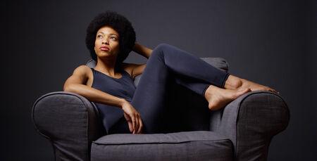 Zwarte vrouw zitten in de stoel denken Stockfoto