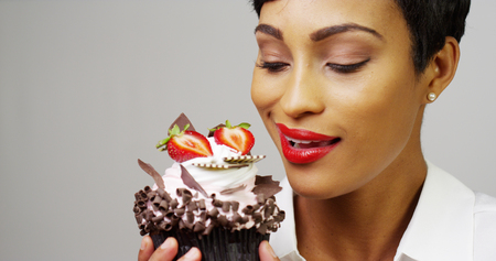 Woman admiring a fancy dessert cupcake with chocolate and strawberries
