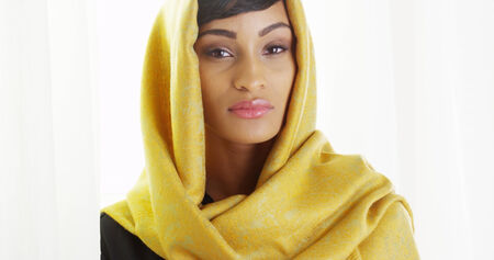 Beautiful African woman wearing gold head scarf in bright room Reklamní fotografie