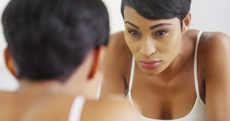 reflexion: Mujer Negro salpicar la cara con agua y mirando en el espejo Foto de archivo