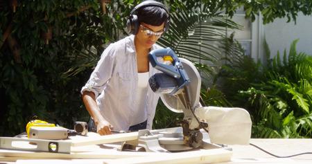2x4: Black woman doing home improvement measuring wood Stock Photo
