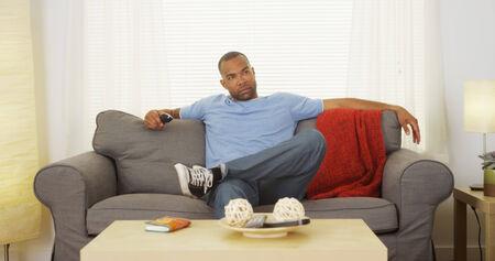 man watching tv: Black man sitting on couch watching tv