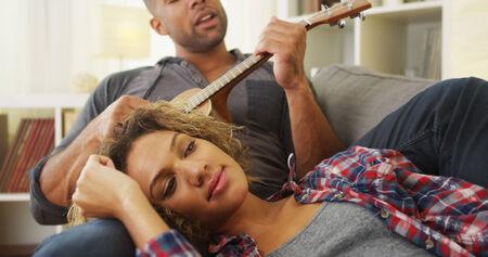 Black girlfriend enjoying being serenaded to by boyfriend photo