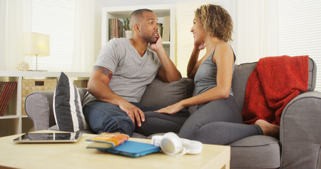 serious: African American couple talking together on couch