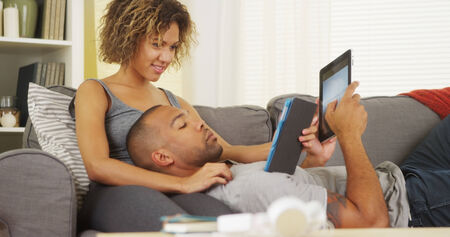 couple couch: African couple using tablets on couch