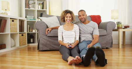 Cute African couple sitting on floor in living room photo