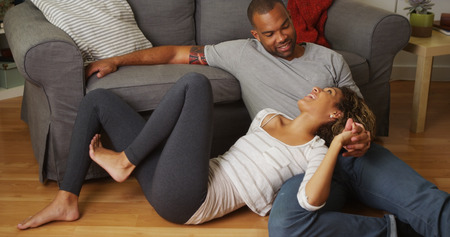 woman sitting on floor: African American couple talking on floor