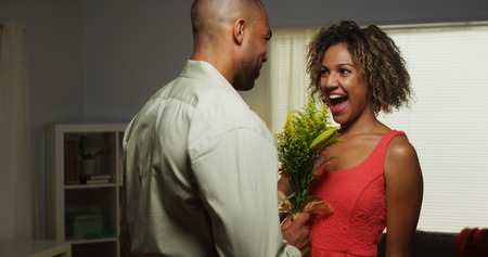 gift behind back: Black boyfriend surprises girlfriend with flowers