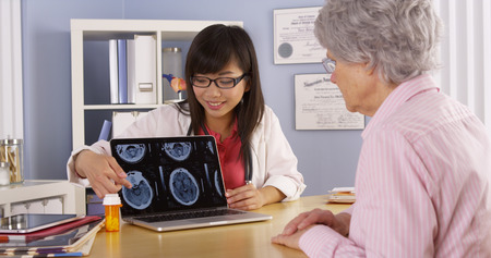 Asian doctor explaining brain scans to elderly patient photo
