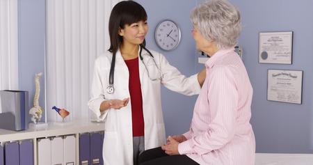 Chinesische Arzt im Gespräch mit älteren Patienten