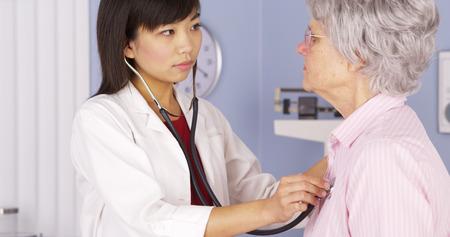 pacientes: Doctor chino que escucha el coraz�n del paciente de edad avanzada
