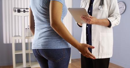 donne obese: Medico maggiore che comunica con il paziente in sovrappeso messicana