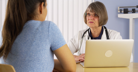 advising: Senior doctor advising Mexican woman patient Stock Photo