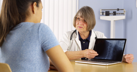 Senior doctor explaining neck x-ray to Mexican woman patient photo