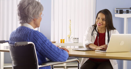 mature mexican: Mexican woman doctor talking with elderly patient