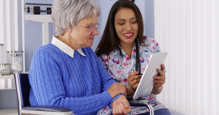 Mexican caregiver sharing tablet with elderly patient Stock Photo