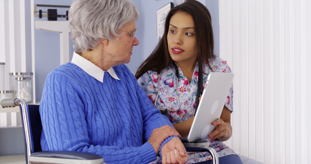 Hispanic caregiver sharing tablet with elderly patient