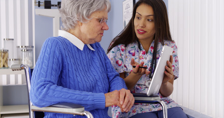mature mexican: Mexican caregiver talking with tablet with elderly patient