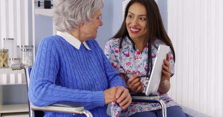 Friendly Mexican caregiver talking to elderly patient with tablet