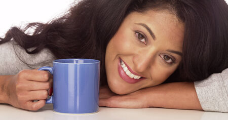 Happy Hispanic woman with coffee photo