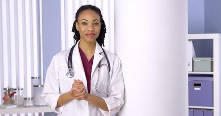Friendly black woman doctor standing in office