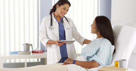 recovering: Hispanic female doctor talking to African patient Stock Photo