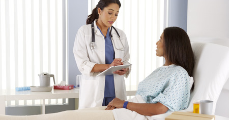 happy doctor woman: Female doctor talking to African American patient in hospital bed Stock Photo