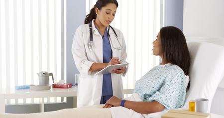 Weibliche Arzt im Gespräch mit African American Patienten im Krankenhausbett