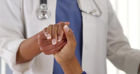 manos entrelazadas: Primer plano de mujer médico sosteniendo la mano del paciente africano americano