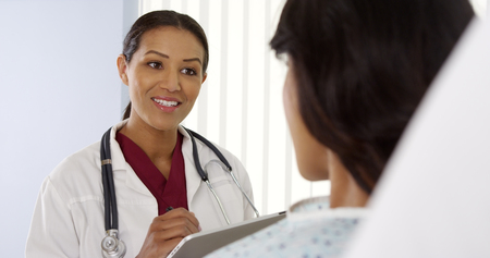 Female doctor talking to Hispanic patient with tablet computer
