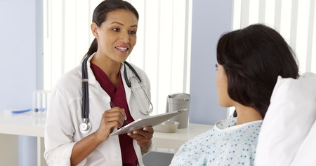 hispanic girls: Female African doctor talking to Hispanic patient using tablet computer Stock Photo