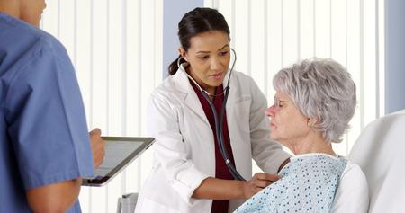 persona respirando: African American m�dico escucha el coraz�n del paciente anciano con estetoscopio