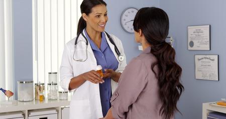 African American doctor explaining prescription to Hispanic patient