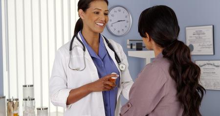 obgyn: Black doctor explaining prescription medicine to female patient Stock Photo