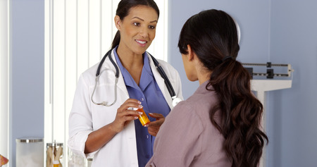Black doctor talking to female patient about new prescription