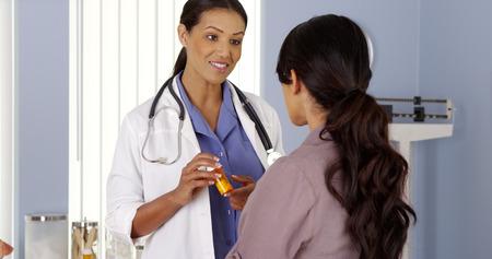 Schwarz Arzt im Gespräch mit weiblichen Patienten über neue verschreibungspflichtige