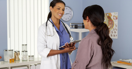 hispanics: African American gynecologist talking to patient with tablet