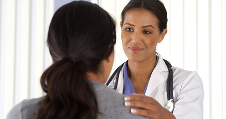 Close up of African American doctor talking to female patient Stock Photo