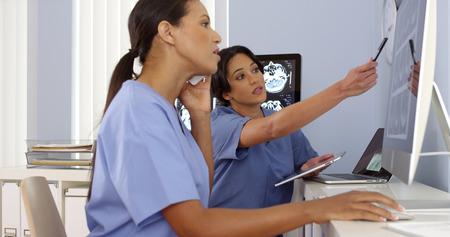 African American Hispanic und die Ärzte, die zusammen an Computer und Telefon