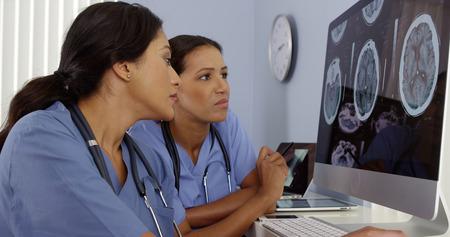 Dos médicos revisar las imágenes del cerebro en los equipos del hospital Foto de archivo - 33804647
