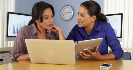 African and Hispanic bsuiness women using laptop and tablet computer in office Stock Photo
