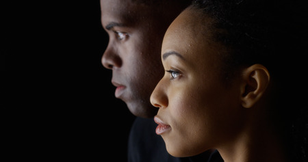 woman serious: Dramatic side view of two young African American people on black background