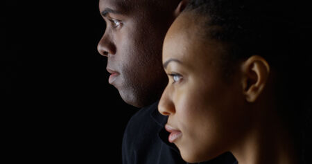 Dramatic profile rack focus of two young black people Standard-Bild