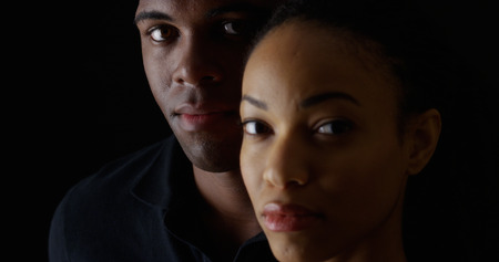 woman black background: Dramatic rack focus between two young African Americans Stock Photo