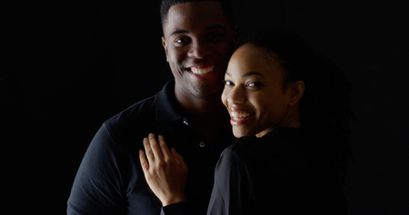 african fashion: Dramatic portrait of young Black couple holding each other smiling