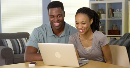 Happy young black couple laughing and watching funny video on laptop
