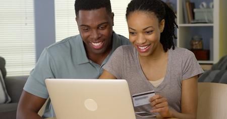 젊은 흑인 부부 사용하여 신용 카드 웃는 온라인 구매를 만들기 위해 스톡 콘텐츠