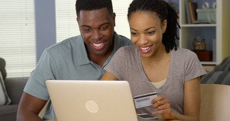 online: Smiling young black couple using credit card to make online purchases