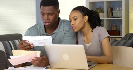 Ernste junge schwarze Paar Zahlung von Rechnungen online mit Laptop-Computer