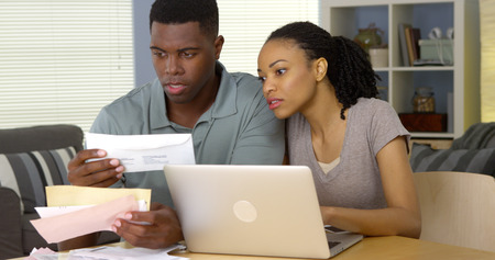 pay desk: Serious young black couple paying bills online with laptop computer
